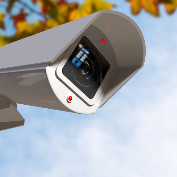 A white wireless surveillance camera with illuminated lights mounted on a wall in the daytime with copy space